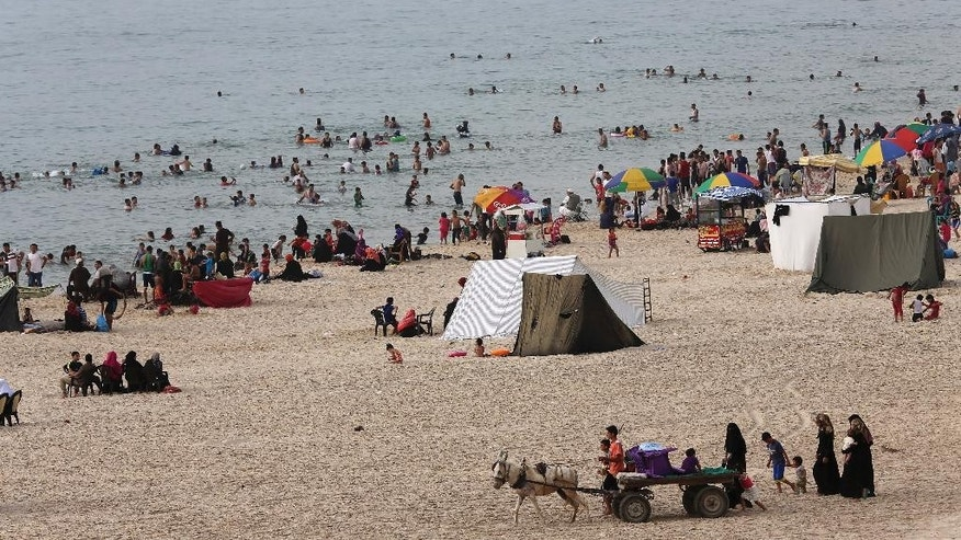 Palestinian families enjoy themselves at the beach of the Mediterranean Sea in Gaza City in the northern Gaza Strip, Wednesday, May 27, 2015. Palestine is experiencing a heat wave with temperatures reaching about 42 degrees Celsius (107.6 degrees Fahrenheit) in the Gaza Strip. (AP Photo/Adel Hana)