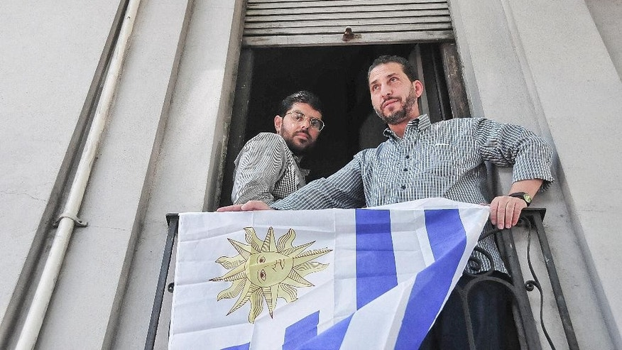 FILE - In this Dec. 11, 2014 file photo, Omar Abdelahdi Faraj, of Syria, left, and Adel bin Muhammad El Ouerghi, of Tunisia, look out at the press from their shared home's balcony decorated with Uruguay's flag in Montevideo, Uruguay. The two former Guantanamo Bay detainees who resettled in Uruguay are planning to tie the knot with women from the South American country. Imam Samir Selim said on Thursday, May 28, 2015 that he would officiate the ceremony. (Ines Guimaraens, Diario El Observador via AP, File) URUGUAY OUT - NOT FOR USE ON URUGUAY WEBSITES OR PUBLICATIONS - NO PUBLICAR EN URUGUAY - NO USAR EN PAGINAS WEBS O EN PAPEL EN URUGUAY