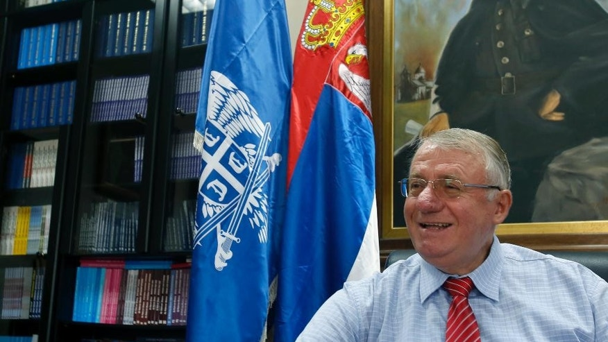 Serbian far right leader Vojislav Seselj smiles during an interview with The Associated Press, in Belgrade, Serbia, Thursday, May 28, 2015. Seselj says he will launch a legal battle before the Serbian courts to fight his pending extradition to the Yugoslav war crimes tribunal. In the background is a portrait of controversial Serb World War II leader Gen. Dragoljub Draza Mihailovic. (AP Photo/Darko Vojinovic)