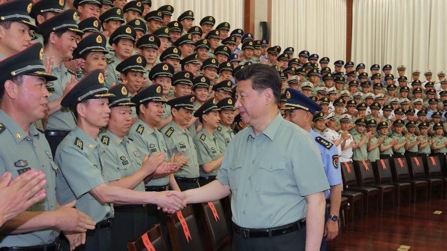 In this Tuesday, May 26, 2015 photo released by China's Xinhua News Agency, Chinese President Xi Jinping, also general secretary of the Communist Party of China (CPC) Central Committee and chairman of the Central Military Commission, meets with senior officers of Zhejiang Military Area Command during an inspection tour in Hangzhou, capital of east China's Zhejiang Province when Xi had a three-day inspection tour in the province. Rapturous crowds. Beaming workers. Pep talks for the troops. The TV coverage Thursday, May 28 of Chinese president's recent visit to the eastern province was a tour de force of Communist propaganda, showcasing what's seen as an emerging cult of personality around the country's strongest leader in decades. (Li Gang/Xinhua via AP)