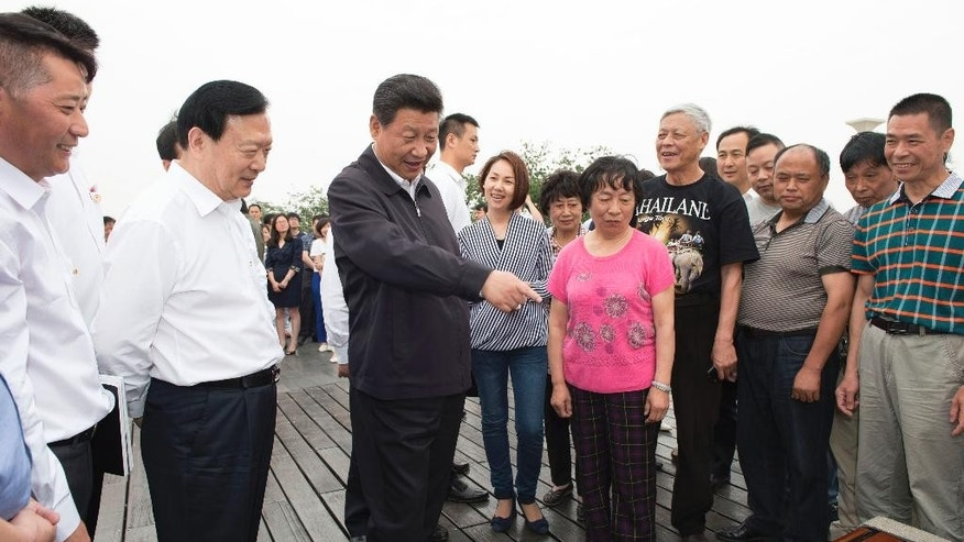 In this Tuesday, May 26, 2015 photo released by China's Xinhua News Agency, Chinese President Xi Jinping talks with local people in Hangzhou, capital of east China's Zhejiang Province when Xi had a three-day inspection tour in the province. Rapturous crowds. Beaming workers. Pep talks for the troops. The TV coverage Thursday, May 28 of Chinese president's recent visit to the eastern province was a tour de force of Communist propaganda, showcasing what's seen as an emerging cult of personality around the country's strongest leader in decades. (Xie Huanchi/Xinha via AP)  NO SALES
