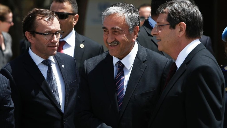 Cyprus President Nicos Anastasiades, right, Turkish Cypriot leader Mustafa Akinci, center, shake hands next to the United Nations envoy Espen Barth Eide, left, after their meeting at a UN compound inside the the U.N buffer zone at the abandoned Nicosia airport in the Cypriot divided capital Nicosia on Thursday, May 28, 2015. The leaders of Cyprus' rival Greek and Turkish Cypriot communities have agreed to open two more crossing points across the island's north-south divide as reunification negotiations ramp up. Cyprus was split in 1974 when Turkey invaded after a coup by supporters of union with Greece. (AP Photo/Petros Karadjias)