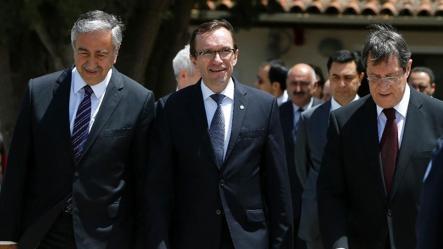 Cyprus President Nicos Anastasiades, right, Turkish Cypriot leader Mustafa Akinci, left, and United Nations envoy Espen Barth Eide, center, leave their talks after a meeting at a UN compound inside the the U.N buffer zone at the abandoned Nicosia airport in the Cypriot divided capital Nicosia on Thursday, May 28, 2015. The leaders of Cyprus' rival Greek and Turkish Cypriot communities have agreed to open two more crossing points across the island's north-south divide as reunification negotiations ramp up. Cyprus was split in 1974 when Turkey invaded after a coup by supporters of union with Greece. (AP Photo/Petros Karadjias)