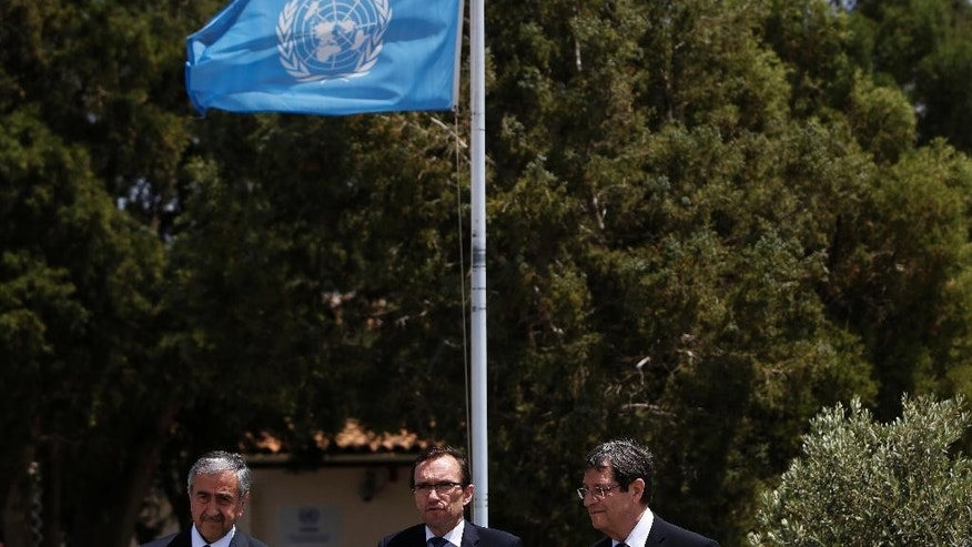 United Nations envoy Espen Barth Eide, center, Cyprus President Nicos Anastasiades, right, and Turkish Cypriot leader Mustafa Akinci, left, make a statement after their meeting at a UN compound inside the the U.N buffer zone at the abandoned Nicosia airport in the Cypriot divided capital Nicosia on Thursday, May 28, 2015. The leaders of Cyprus' rival Greek and Turkish Cypriot communities have agreed to open two more crossing points across the island's north-south divide as reunification negotiations ramp up. Cyprus was split in 1974 when Turkey invaded after a coup by supporters of union with Greece. (AP Photo/Petros Karadjias)