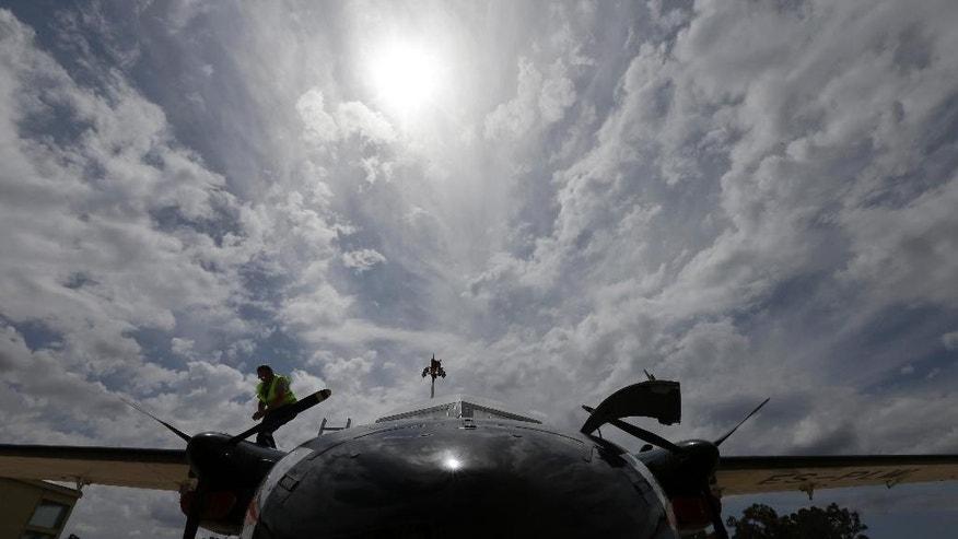 An Estonian mechanic checks the wings of an aircraft at the Military Airport of Kalamata town, Greece, after a Frontex flight patrol operation over the Ionian Sea, southwestern Greece on Wednesday, May 27, 2015. The border agency plans to significantly boost its presence on the Mediterranean from June to September, the high season for migrant crossings. The European Union will seek to shift the migration burden away from Italy and Greece by relocating 40,000 asylum seekers to other EU countries, according to a draft document seen by The Associated Press Tuesday. (AP Photo/Thanassis Stavrakis)
