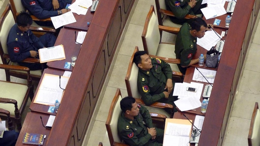 In this April 9, 2015 photo, an army representative dozes off at a parliament session in Naypyitaw, Myanmar. Journalists were negotiating with Myanmar officials Thursday, May 28, 2015 to restore their access to the Parliament chamber after being pushed out because pictures of snoozing lawmakers were published online. Reporters were told on Tuesday, May 26 they would have to watch proceedings on TV from the corridor. The pictures of sleeping MPs was the main reason cited by Kyaw Soe, director general of the Union Parliament, which handles administrative duties. (AP Photo/Khin Maung Win)