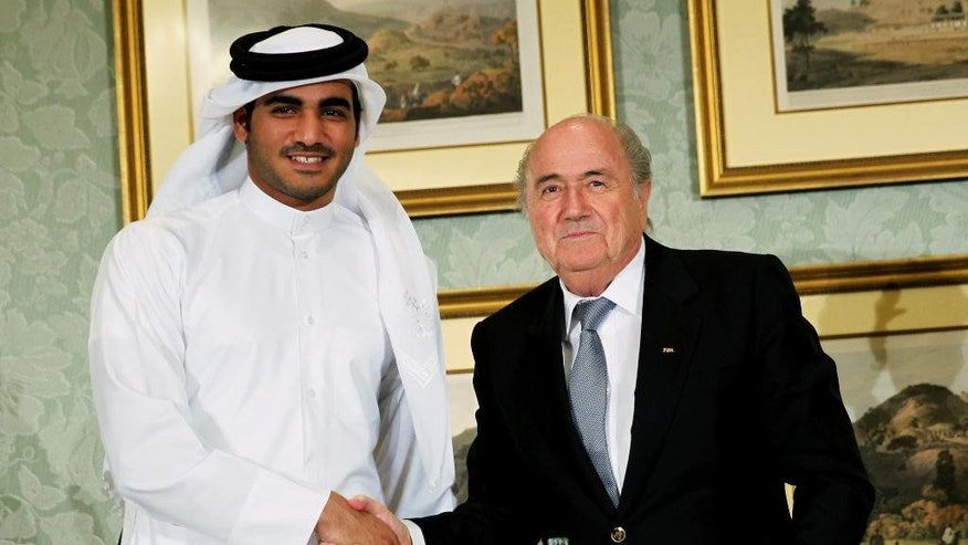 FILE - In this Saturday, Nov. 9, 2013, file photo, FIFA President Sepp Blatter, right, shakes hands with Sheik Mohammed bin Hamad al-Thani, chairman of Qatar 2022 bid committee, at a press conference in Doha, Qatar. Qatar is keeping quiet about the American and Swiss raids that have rocked football's world governing body FIFA and thrown a new unwelcome spotlight on the tiny Gulf nation's hosting of the 2022 World Cup. (AP Photo/Osama Faisal, File)