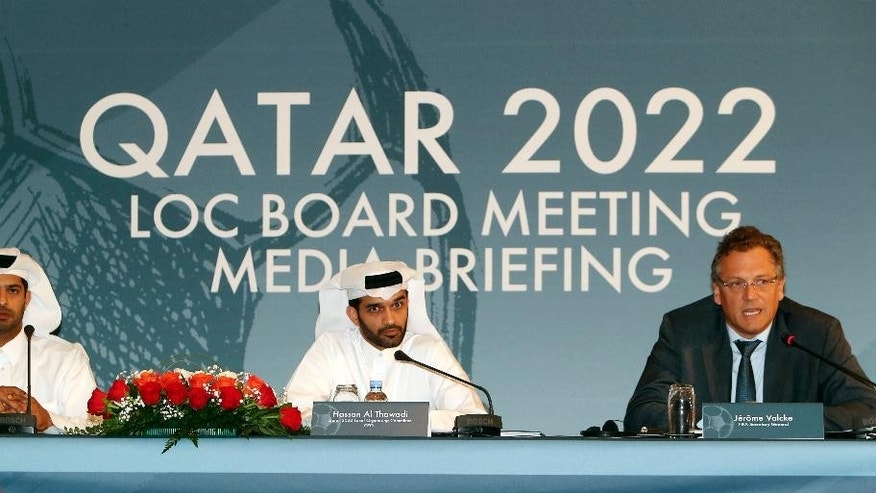 FILE - In this Wednesday, Feb. 25, 2015, file photo, Nasser Al Khater Qatar 2022 Local Organizing Committee Deputy CEO, left, Hassan Al Thawadi, head of the Qatar 2022 World Cup organizing committee, center, and FIFA Secretary General Jerome Valcke give a press conference, in Doha. Qatar is keeping quiet about the American and Swiss raids that have rocked football's world governing body FIFA and thrown a new unwelcome spotlight on the tiny Gulf nation's hosting of the 2022 World Cup.  (AP Photo/Osama Faisal, File)