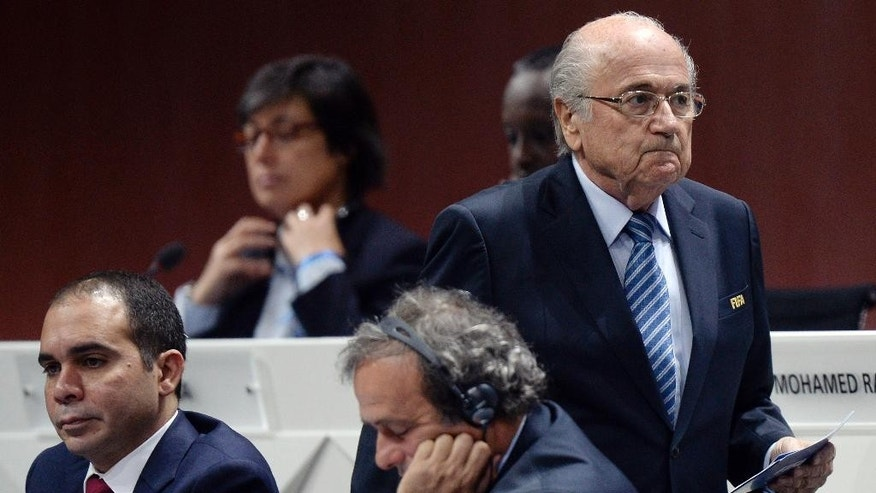 FIFA president Joseph S. Blatter, right, walks past Prince Ali bin al-Hussein, left, and UEFA President Michel Platini, center, during the 65th FIFA Congress held at the Hallenstadion in Zurich, Switzerland, Friday, May 29, 2015, where he will run for re-election as FIFA head. (Walter Bieri/Keystone via AP)