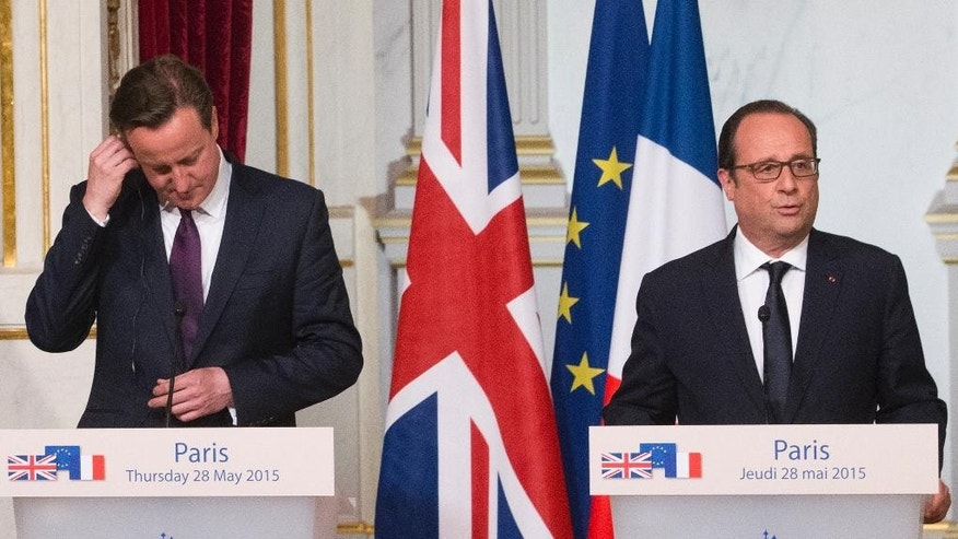 Britain's Prime Minister, David Cameron, left, adjusts his earpiece as French President, Francois Hollande, speaks during a joint press conference, at the Elysee Palace in Paris, Thursday May 28, 2015. (AP Photo/Jacques Brinon)