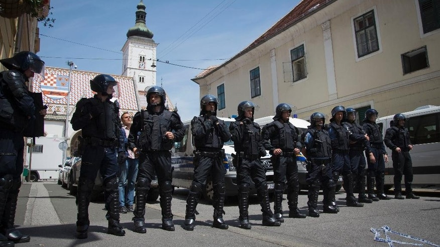 Police in riot gear blocks access to St. Mark church in Zagreb, Croatia, Friday, May 29, 2015. Over 100 Croatian war veterans have taken refuge inside a church after police disrupted their anti-government protest in central Zagreb. The nationalist veterans from Croatia's war for independence in the 1990s, who have been campaigning for more rights since September, were demanding to speak to prime minister. (AP Photo/Darko Bandic)
