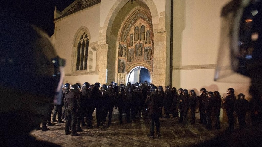 In this photo taken late Thursday May 28, 2015, police in riot gear attempts to enter St. Mark church in Zagreb, Croatia. Over 100 Croatian war veterans have taken refuge inside a church after police disrupted their anti-government protest in central Zagreb. The nationalist veterans from Croatia's war for independence in the 1990s, who have been campaigning for more rights since September, were demanding to speak to prime minister. (AP Photo/Darko Bandic)