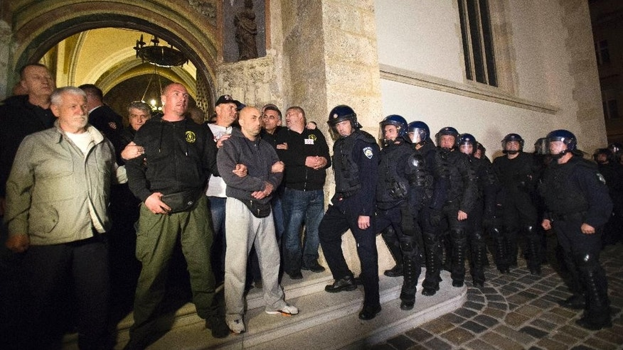 In this photo taken late Thursday May 28, 2015, a group of war veterans prevents police to enter St. Mark church in Zagreb, Croatia. Over 100 Croatian war veterans have taken refuge inside a church after police disrupted their anti-government protest in central Zagreb. The nationalist veterans from Croatia's war for independence in the 1990s, who have been campaigning for more rights since September, were demanding to speak to the prime minister. (AP Photo/Darko Bandic)