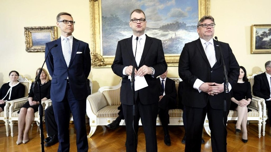 New Finnish Prime Minister Juha Sipila, centre, Finance Minister Alexander Stubb, left  and Foreign Minister Timo Soini  his cabinet attend a press conference in Helsinki, Finland on Friday  May 29, 2015. Finland's new three-party coalition government took office on Friday. ( Antti Aimo-Koivisto/LEHTIKUVA via AP) FINLAND OUT