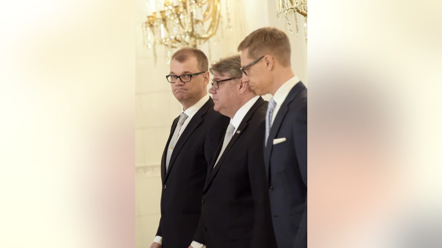 New Finnish Prime Minister, Centre Party's chairman Juha Sipila, left, and his government, Foreign Minister Timo Soini, center, and Finance Minister Alexander Stubb arrive at the Presidental Palace in Helsinki, Finland, Friday, May 29, 2015 during a visit to the Presidential Palace. Finland's new three-party coalition government took office on Friday. (Vesa Moilanen/Lehtikuva via AP)    FINLAND OUT