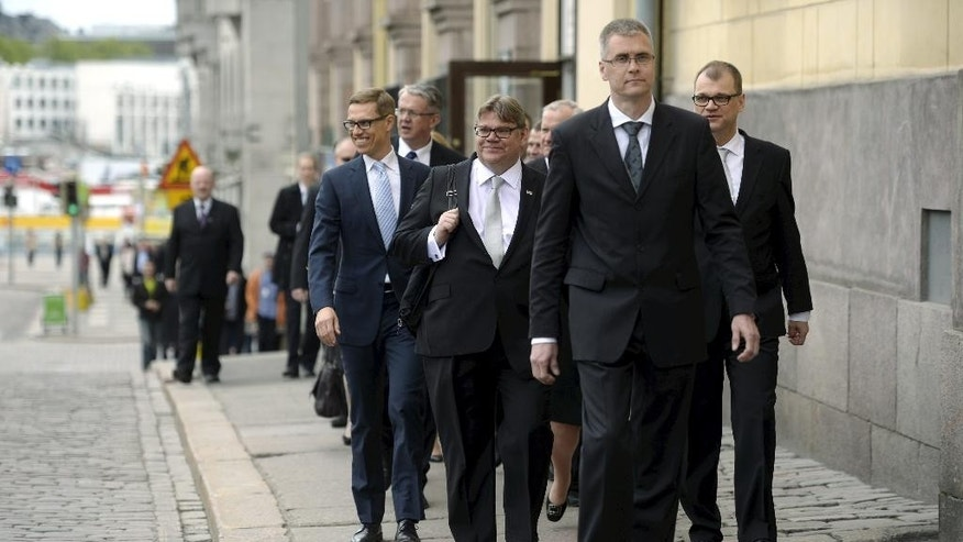 New Finnish Prime Minister, Centre Party's chairman Juha Sipila, right, and his government walk to a press conference in Helsinki, Finland, Friday, May 29, 2015. Finland's new three-party coalition government took office on Friday. On the left new Finance Minister Alexander Stubb and Foreing Minister Timo Soini. (Antti Aimo-Koivisto/Lehtikuva via AP)    FINLAND OUT