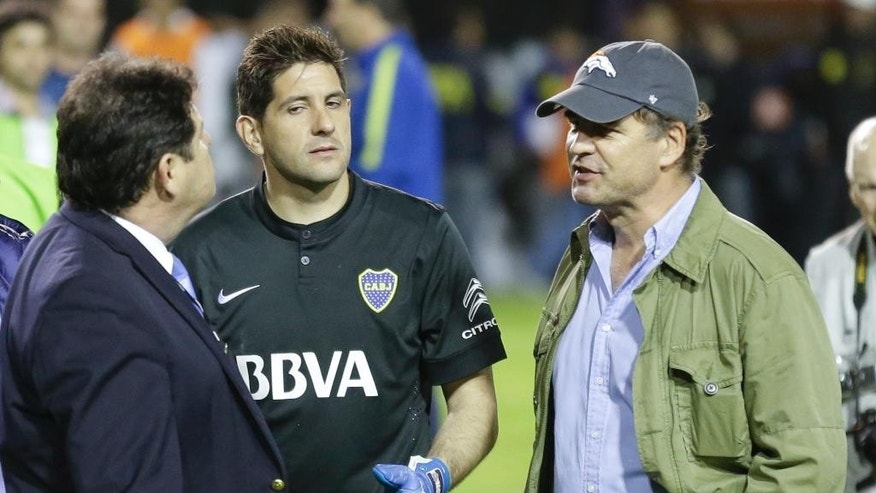 In this May 14, 2015 photo, Conmebol delegate Roger Bello of Bolivia, left, talks with Boca Juniors goalkeeper Agustin Orion, center, and Alejandro Burzaco, right, president of Torneos y Competencias, moments before canceling the Copa Libertadores soccer match between Boca Juniors and River Plate in Buenos Aires, Argentina. A US Justice Department indictment was announced Wednesday, May 27, 2015, against nine FIFA officials and several corporate executives for racketeering, conspiracy and corruption. Burzaco is one of the sports marketing executives charged. (AP Photo/Victor R. Caivano)
