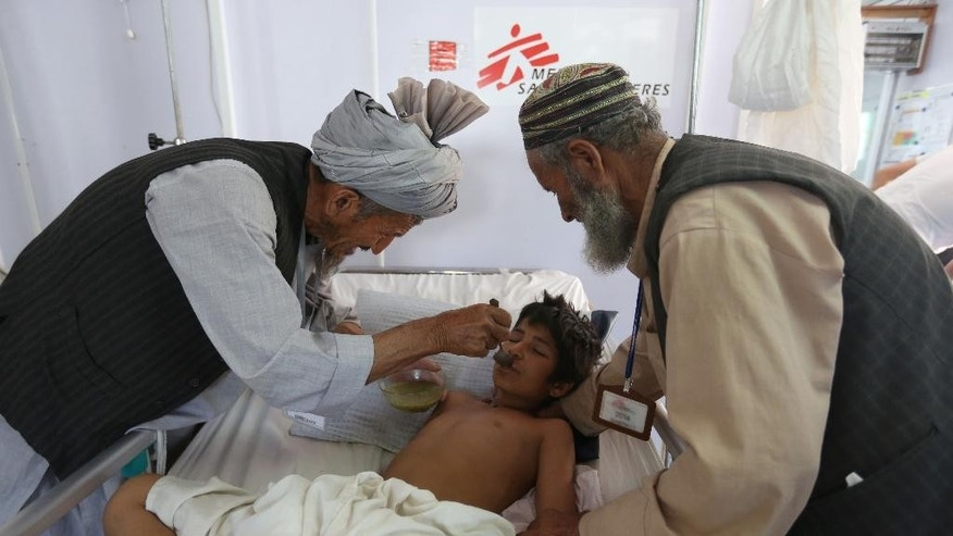 In this Wednesday, May 20, 2015 photo, an Afghan boy is fed as he recovers at a Medecins Sans Frontieres  (MSF) hospital in Kunduz province, north of Kabul, Afghanistan. When the Taliban descended a month ago on Dam Shakh, a hamlet on the wheat-growing plains of northern Afghanistan's Kunduz province, nobody was prepared. By the time they were beaten back from the provincial capital of Kunduz, more than 100,000 people were forced from their homes and total of 204 war-wounded were admitted to Kunduz's only trauma hospital, run by French NGO, MSF in less than a month. (AP Photo/Rahmat Gul)