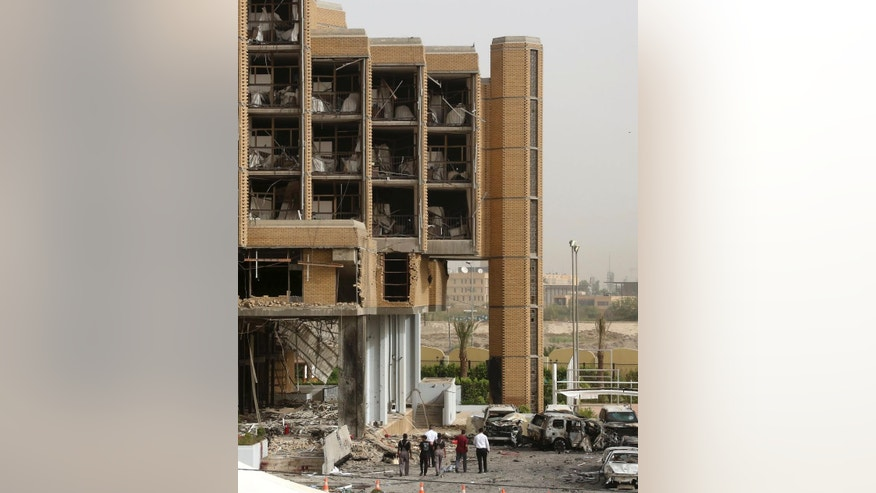Civilians and security forces inspect the aftermath of a car bomb attack in the parking lot of Babylon  hotel in Baghdad, Iraq, Friday, May 29, 2015. Two separate car bombs inside parking lots of two downtown hotels have killed and wounded civilians late Thursday, authorities said. (AP Photo/Hadi Mizban)