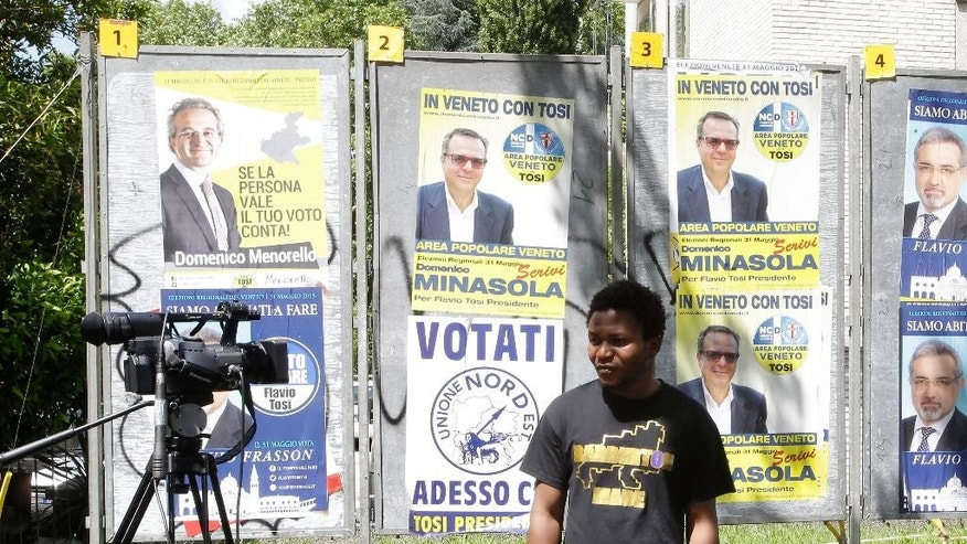 In this picture taken on Wednesday, May 27, 2015, Issa Konate, from Mali, attends an interview with The Associated Press past election posters near a migrant holding center in Baone, near Padua, northern Italy Housing migrants who continue to flood Italy, many risking death in Mediterranean crossings, has become a contentious campaign issue in Italian regional elections set for Sunday. It has unleashed a wave of anti-migrant resentment that Matteo Salvini, the up-and-coming leader of the populist Northern League, has both benefited from and fomented. (AP Photo/Antonio Calanni)