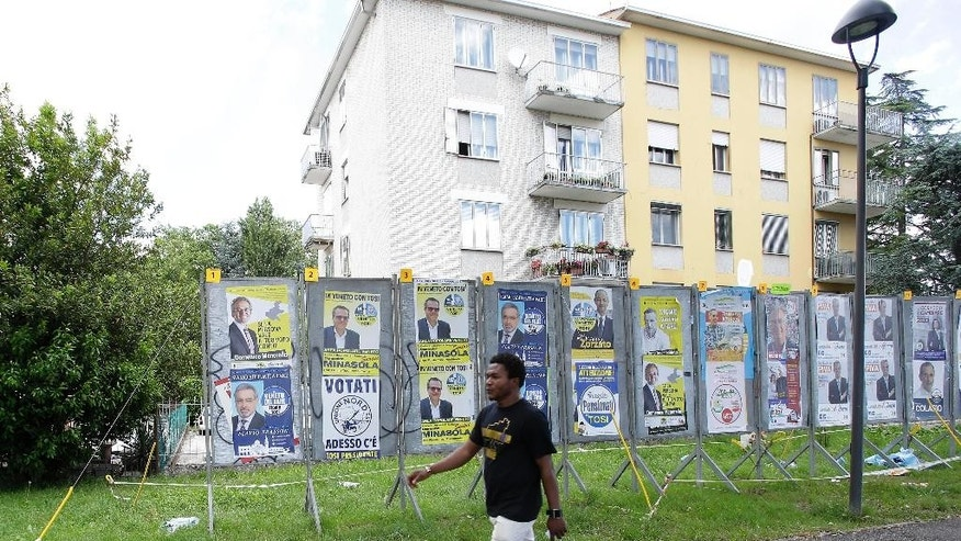In this picture taken on Wednesday, May 27, 2015, Issa Konate, from Mali, walks past election posters near a migrant holding center in Baone, near Padua, northern Italy. Housing migrants who continue to flood Italy, many risking death in Mediterranean crossings, has become a contentious campaign issue in Italian regional elections set for Sunday. It has unleashed a wave of anti-migrant resentment that Matteo Salvini, the up-and-coming leader of the populist Northern League, has both benefited from and fomented. (AP Photo/Antonio Calanni)
