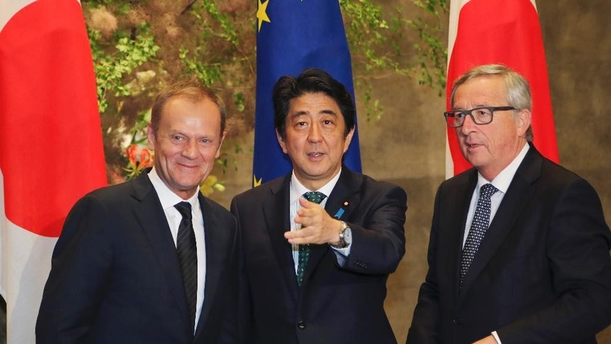 European Council President Donald Tusk, left, European Commission President Jean-Claude Juncker, right, and Japanese Prime Minister Shinzo Abe wait for the arrival of Abe's Cabinet members for a group photo session prior to their meeting at Abe's official residence in Tokyo Friday, May 29, 2015. (AP Photo/Koji Sasahara, Pool)