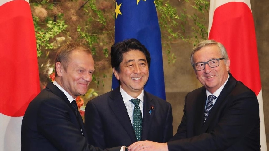 European Council President Donald Tusk, left, and European Commission President Jean-Claude Juncker, right, shake hands with Japanese Prime Minister Shinzo Abe prior to their meeting at Abe's official residence in Tokyo Friday, May 29, 2015. (AP Photo/Koji Sasahara, Pool)