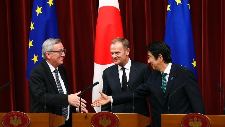 Japan' Prime Minister Shinzo Abe, right, reaches out to shake hands with European Commission President Jean-Claude Juncker, left, as European Council President Donald Tusk smiles at the end of a joint news conference following a Japan-EU summit meeting in Tokyo Friday, May 29, 2015.  (Thomas Peter/Pool Photo via AP)