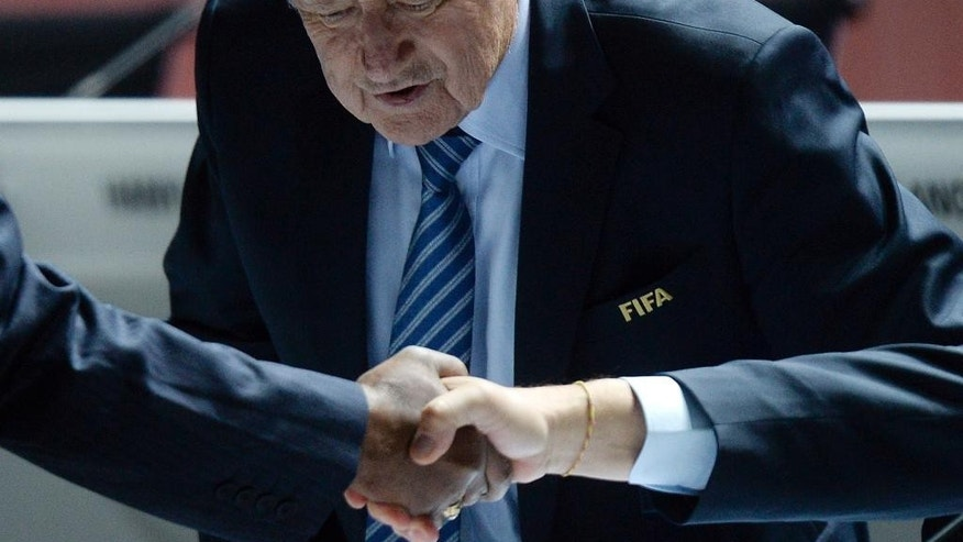 FIFA president Joseph S. Blatter takes a seat as people shake hands in front of him during the 65th FIFA Congress held at the Hallenstadion in Zurich, Switzerland, Friday, May 29, 2015, where he will run for re-election as FIFA head. (Walter Bieri/Keystone via AP)