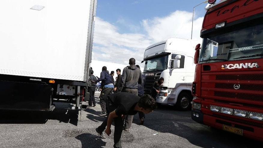 Afghan migrants run for  cover during a Coast Guard patrol, as they attempt to board trucks heading to Italy from the southern Greek city of Patras, Thursday, May 28, 2015. In an effort to help manage more than 80,000 people who have landed on European shores so far this year, mostly in Italy and Greece, the EU's executive Commission is proposing to relocate thousands of refugees to other member countries and wants to launch a security operation in the Mediterranean to eliminate the trafficking operations. (AP Photo/Thanassis Stavrakis)