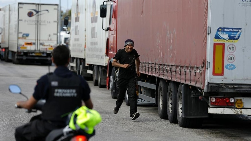 An Afghan migrant runs to avoid a security at the southern Greek city of Patras, on Thursday, May 28, 2015. In an effort to help manage more than 80,000 people who have landed on European shores so far this year, mostly in Italy and Greece, the EU's executive Commission is proposing to relocate thousands of refugees to other member countries and wants to launch a security operation in the Mediterranean to eliminate the trafficking operations. (AP Photo/Thanassis Stavrakis)