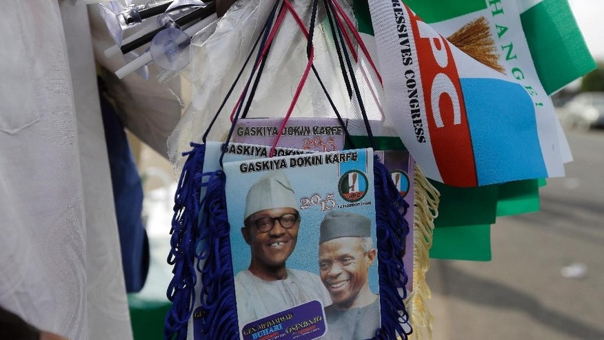 A man sells banners of former General and Nigerian President elect, Muhammadu Buhari, and Vice President elect Yemi Osibajo, outside Eagle Square, a day ahead of the Presidential Inauguration of Buhari, in Abuja,  Nigeria, Thursday, May 28, 2015. (AP Photo/Sunday Alamba)