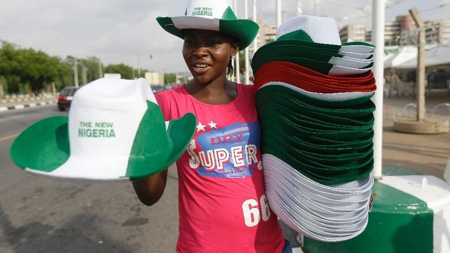 A Woman sells hats, a day ahead of the Presidential Inauguration of former General Muhammadu Buhari, in Abuja , Nigeria, Thursday, May 28, 2015. (AP Photo/Sunday Alamba)