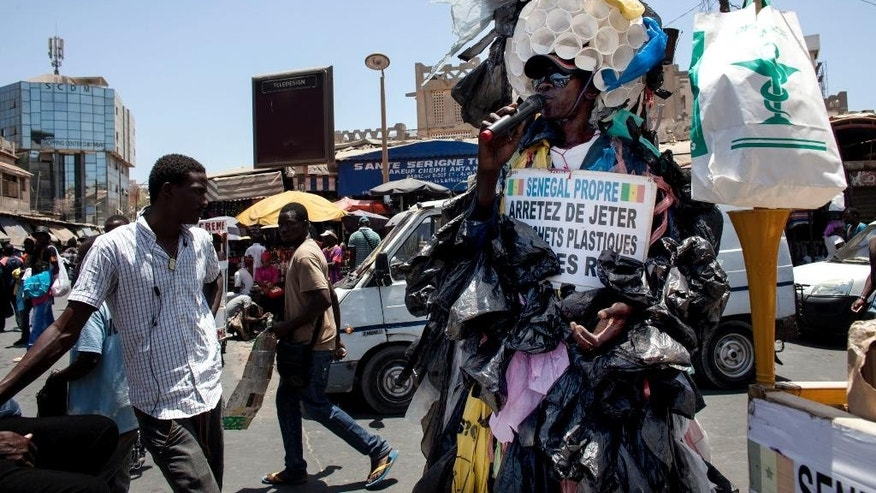 In this photo taken on Thursday, May 28, 2015, Modou Fall, right, clad  in more than 7,000 thin plastic sacks and a dome cap made from 100 plastic cups stapled together, speaks on a microphone as he tries to get Senegalese to stop littering and quit using plastic bags, in Dakar, Senegal. Thin plastic shopping bags, and pieces of them, litter this seaside capital and the nearby waters of the Atlantic Ocean. The number of discarded bags is staggering _ a total of 5 million in Senegal, according to Environment Minister Abdoulaye Balde. Now, the government is set to impose a ban, joining a global shift against the bags. (AP Photo/Jane Hahn)