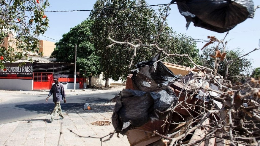 A man passes a tree with plastic bags hanging from it  in Dakar, Senegal, Friday, May 29, 2015. Thin plastic shopping bags, and pieces of them, litter this seaside capital and the nearby waters of the Atlantic Ocean. The number of discarded bags is staggering _ a total of 5 million in Senegal, according to Environment Minister Abdoulaye Balde. Now, the government is set to impose a ban, joining a global shift against the bags. (AP Photo/Jane Hahn)