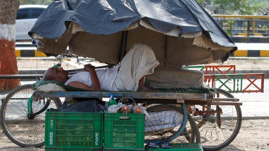 An Indian man rests on a hand cart under a market umbrella on a hot day in Ahmadabad, India, Thursday, May 28, 2015. Eating onions, lying in the shade and splashing into rivers, Indians were doing whatever they could Thursday to stay cool during a brutal heat wave that has killed more than 1,000 in the past month. (AP Photo/Ajit Solanki)