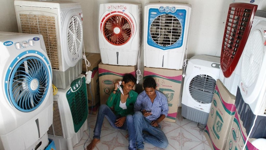 Salesboys sit in a shop selling air coolers on a hot summer day in Ahmadabad, India, Thursday, May 28, 2015. Eating onions, lying in the shade and splashing into rivers, Indians were doing whatever they could Thursday to stay cool during a brutal heat wave that has killed more than 1,000 in the past month. (AP Photo/Ajit Solanki)