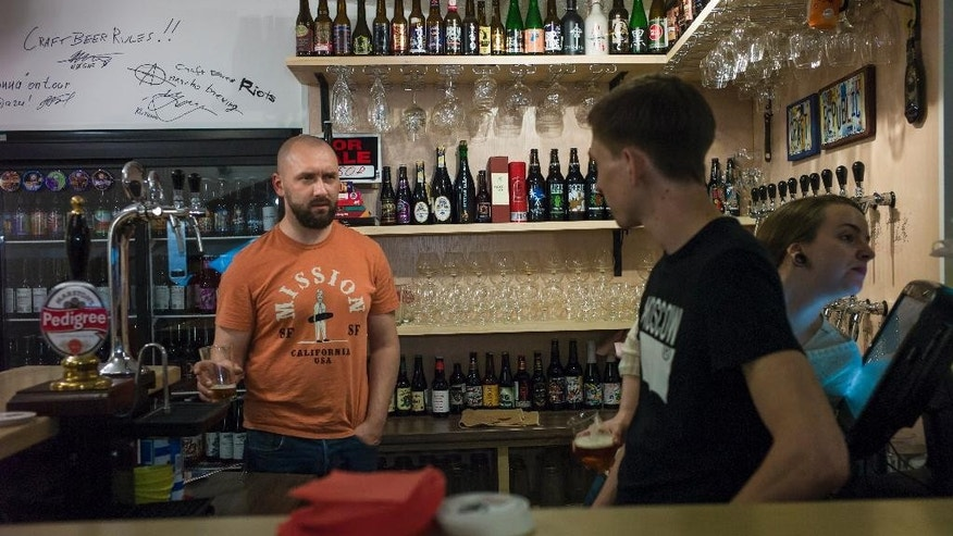 In this photo taken on Friday, May  22, 2015,  Stanislav Obraztsov, left, speaks to his colleagues at his craft beer bar in Moscow. The ruble's crash in value against the dollar last year helped Russia's nascent craft beer industry by making imported competitors more expensive. (AP Photo/Alexander Zemlianichenko)