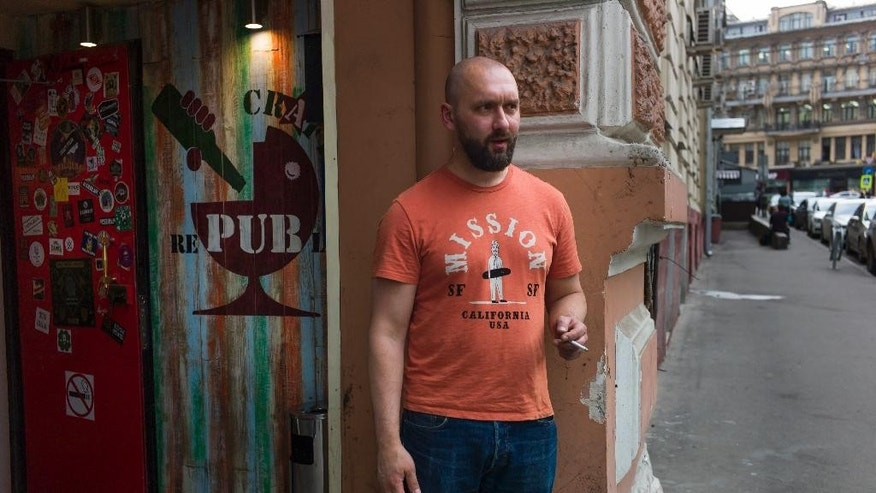 In this photo taken on Friday, May  22, 2015,  Stanislav Obraztsov, takes a break outside his craft beer bar in Moscow. The ruble's crash in value against the dollar last year helped Russia's nascent craft beer industry by making imported competitors more expensive. (AP Photo/Alexander Zemlianichenko)