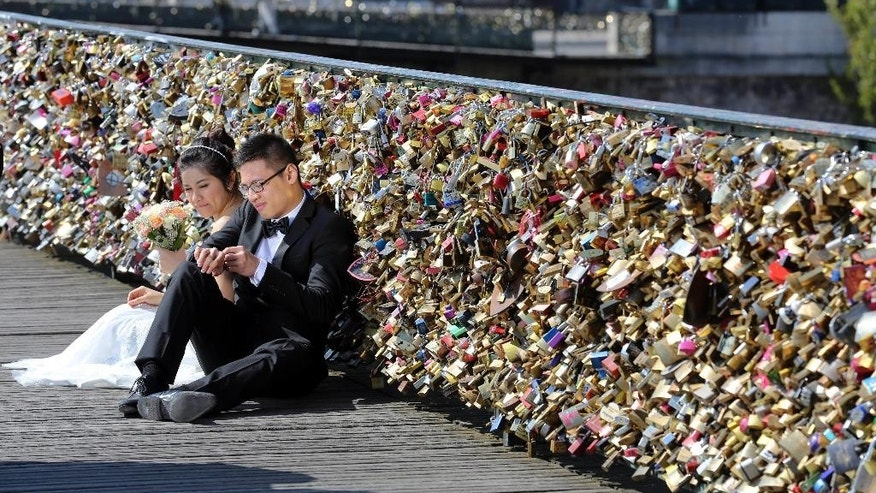 FILE - This Wednesday April 16, 2014 file photo shows a newly wed couple resting on the Pont des Arts in Paris, France. Any hope that the love locks that cling to Paris' famed Pont des Arts bridge would last forever _ will be unromantically dashed by the city council who plan to dismantle them Monday _ for good. (AP Photo/Remy de la Mauviniere, File)