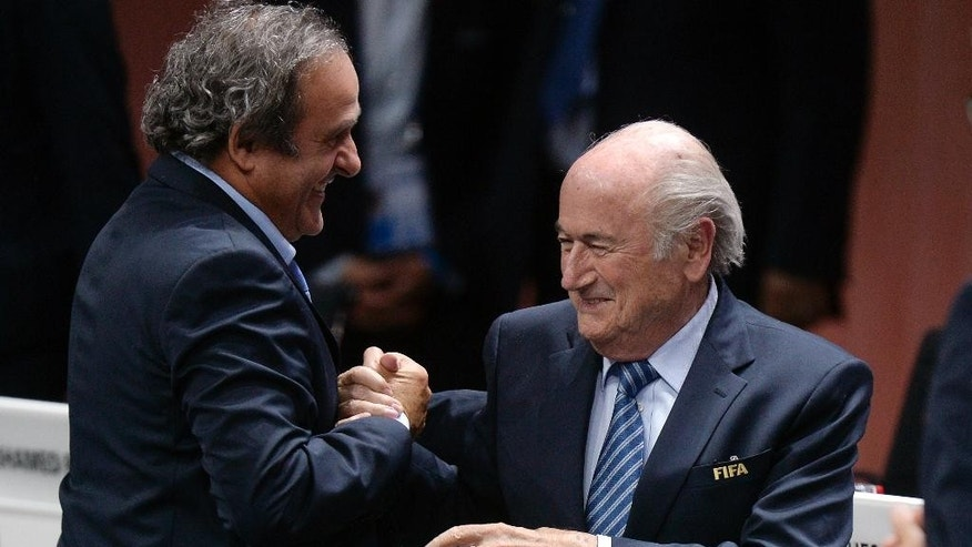 Re-elected FIFA president Sepp Blatter, right,  is congratulated by FIFA vice president and UEFA president Michel Platini after his speech during the 65th FIFA Congress held at the Hallenstadion in Zurich, Switzerland, Friday, May 29, 2015. Blatter has been re-elected as FIFA president for a fifth term, chosen to lead world soccer despite separate U.S. and Swiss criminal investigations into corruption. The 209 FIFA member federations gave the 79-year-old Blatter another four-year term on Friday after Prince Ali bin al-Hussein of Jordan conceded defeat after losing 133-73 in the first round.  (Patrick B. Kraemer / Keystone via AP)