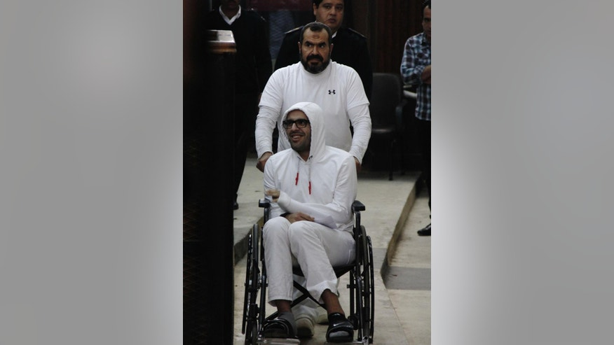 "In this March 9, 2015 photo, Mohammed Soltan is pushed by his father Salah during a court appearance in Cairo, Egypt. Egyptian officials say authorities have freed Soltan, a dual U.S.-Egyptian citizen, Saturday May 30, 2015, Soltan  had been sentenced to life in prison on charges of financing an anti-government sit-in and spreading ""false news."" (AP Photo/Heba Elkholy) ***EGYPT OUT***"