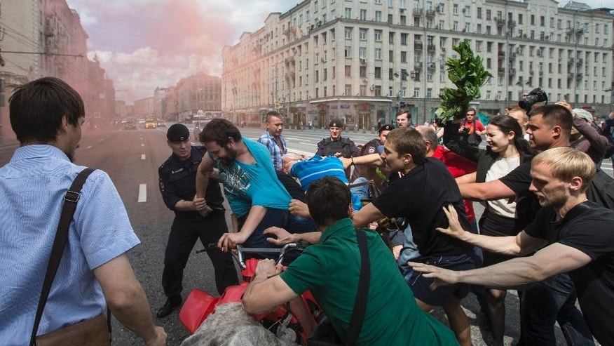 Russian anti-gay demonstrators attack a quad bike driven by gay rights activists as police detain gay rights activists during an attempt to hold a gay demonstration in central Moscow, Russia, Saturday, May 30, 2015. Such meetings, not permitted by the Moscow city authorities, are marked by police interference and resulting detention several activists of the movement. (AP Photo/Pavel Golovkin)