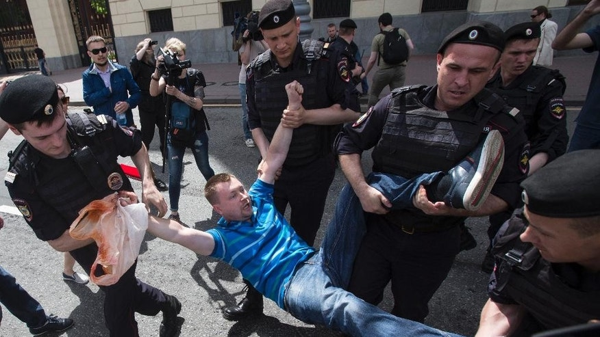 Russian police officers detain gay rights activist Nikolai Alexeyev during an attempt to hold a gay demonstration in Moscow, Russia, Saturday, May 30, 2015. Such meetings, not permitted by the Moscow city authorities, are marked by police interference and resulting detention several activists of the movement. (AP Photo/Pavel Golovkin)