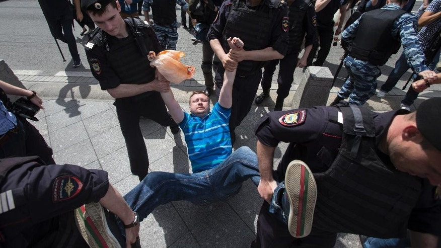 Russian police officers detain gay rights activist Nikolai Alexeyev during an attempt to hold a gay demonstration in Moscow, Russia, Saturday, May 30, 2015. Such meetings, not permitted by the Moscow city authorities, are marked by police interference and resulting detention of several activists of the movement. (AP Photo/Pavel Golovkin)