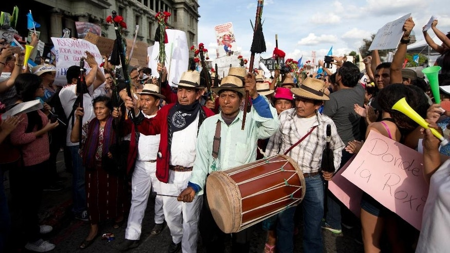 Indigenous authorities from Nebaj village join a protest demanding the resignation Guatemala's President Otto Perez Molina in Guatemala City, Saturday, May 30, 2015. Protesters are demanding the president step down after his Vice President Roxana Baldetti resigned earlier this month amid a corruption scandal. (AP Photo/Moises Castillo)
