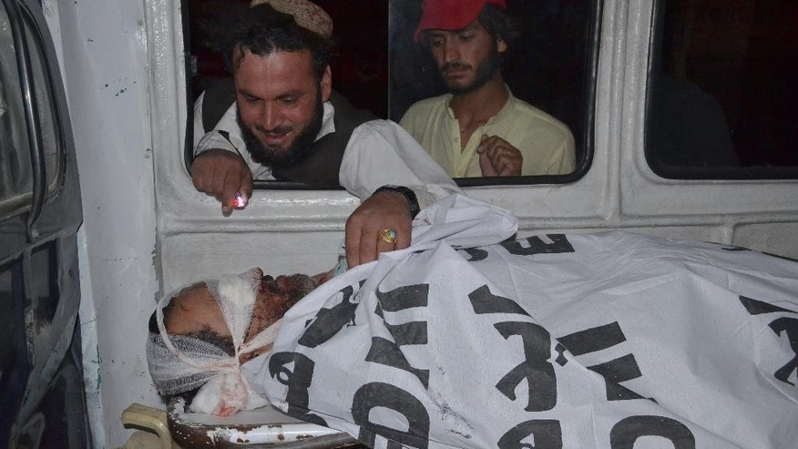 A Pakistani looks the lifeless body of his relative, who was killed by gunmen when they hijacked two buses, as the bodies of victims are brought Quetta, Pakistan, Saturday May 30, 2015. Officials say Pakistani security forces have launched a major operation to hunt down gunmen who hijacked two buses and killed more than a dozen passengers in the country's southwest before fleeing. (AP Photo/Arshad Butt)