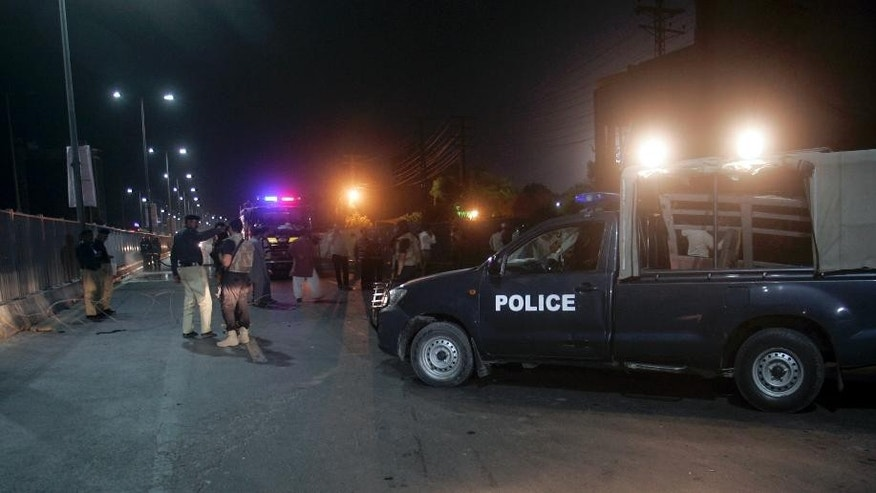 Pakistani police officers gather at the site of  suicide bombing on a road leading to Gaddafi Stadium late night on Friday, May 29, 2015 in Lahore, Pakistan. A suicide bomber blew himself up Friday near a stadium in Lahore where a cricket match was underway between Pakistan and Zimbabwe, killing a police officer and wounding six, Pakistani Information Minister Pervez Rashid told a local news channel. (AP Photo)