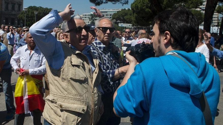 A photographer is attacked by a right-wing demonstrator just before his camera was knocked to the ground during protest in Madrid, Spain, Saturday, May 30, 2015.  Protesters unhappy with the recent election results in which two new parties have carved out a kingmaker role in many Spanish cities and regions following local elections that dealt a serious blow to the governing conservative Popular Party. (AP Photo/Paul White)