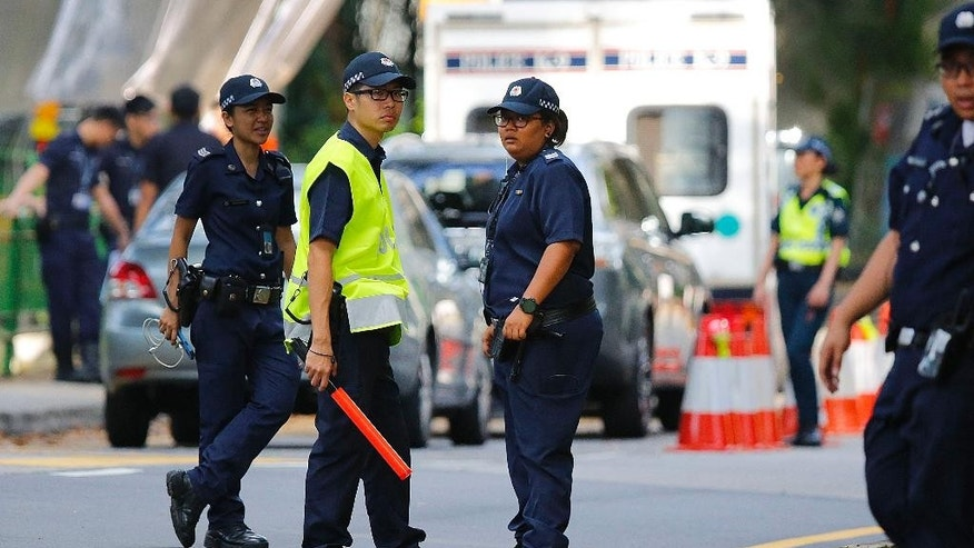 Singapore policemen secure an entry point as they stop pedestrians and attendees of the 14th International Institute for Strategic Studies Shangri-la Dialogue, or IISS, Asia Security Summit, from entering the vicinity, Sunday, May 31, 2015, in Singapore. Police stepped up security around the venue of the international security conference Sunday following a shootout at a roadblock in which officers fatally shot one man and detained two others. The security conference, a major event in the Asia-Pacific region attended by U.S. Secretary of Defense Ash Carter and delegates from dozens of countries from around the world, was uninterrupted but access to the venue was restricted. (AP Photo/Wong Maye-E)